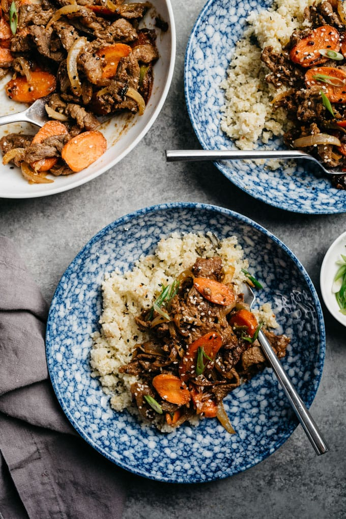 Healthy Whole30 bulgogi over cauliflower rice on a cement table with a grey napkin and garnish bowls of sesame seeds and green onions.