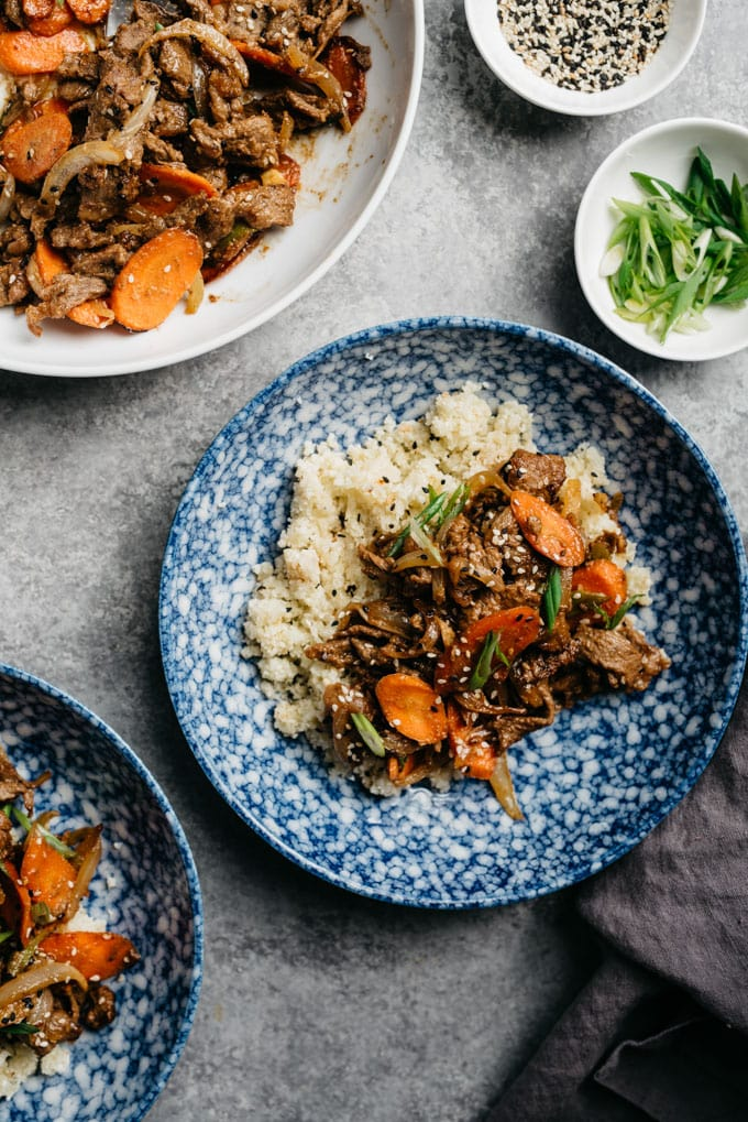 Healthy beef bulgogi over cauliflower rice in a blue bowl with a grey linen napkin and garnish bowls of sesame seeds and green onions.