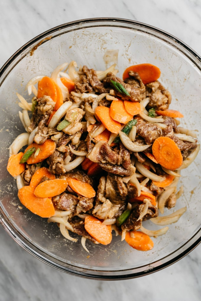 Whole30 bulgogi marinated sirloin in a mixing bowl tossed with onions, carrots, and green onions before being stir fried.