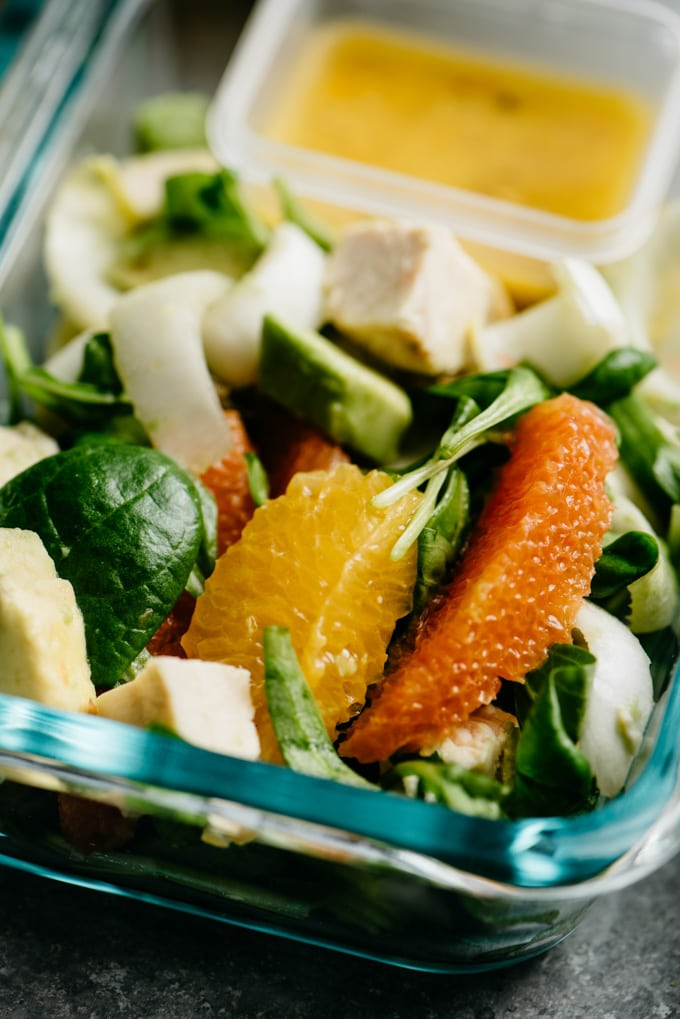 A close up image of orange chicken salad meal prep with endive, almonds, and avocado.