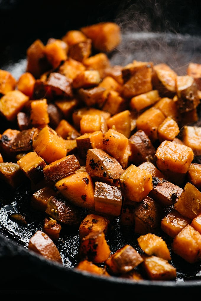 Seared cubes of sweet potatoes in a cast iron skillet.