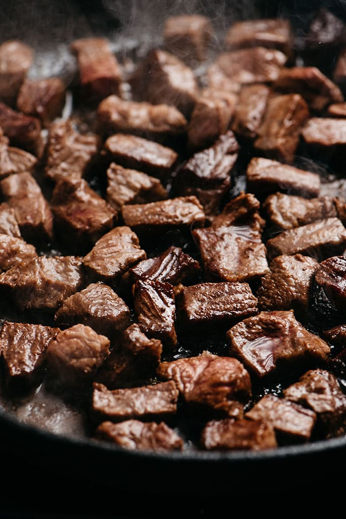 Seared pieces of diced flat iron steak in a cast iron skillet for making Whole30 steak bites.