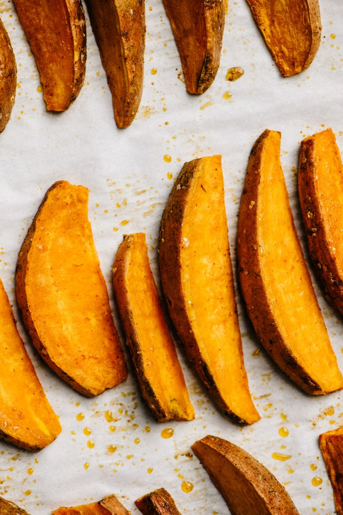 Baked crispy sweet potato fries on a parchment lined baking sheet.