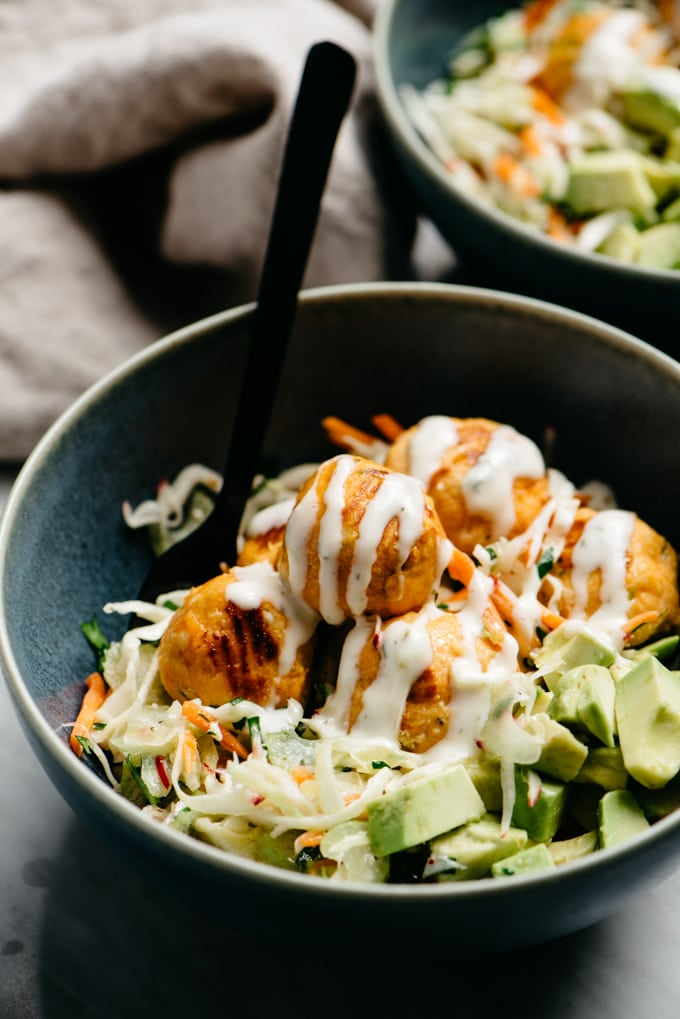 Gluten free buffalo chicken meatballs over a bed of no mayo coleslaw with avocado and ranch dressing in a blue bowl.