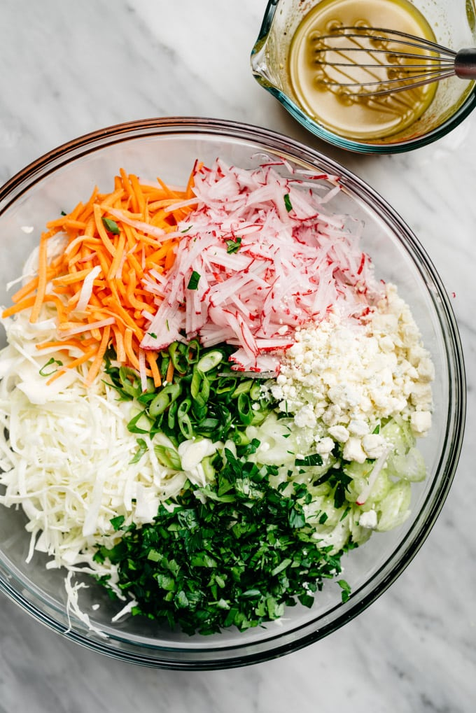 The ingredients for no mayo coleslaw in a mixing bowl to serve with gluten free buffalo chicken meatballs.