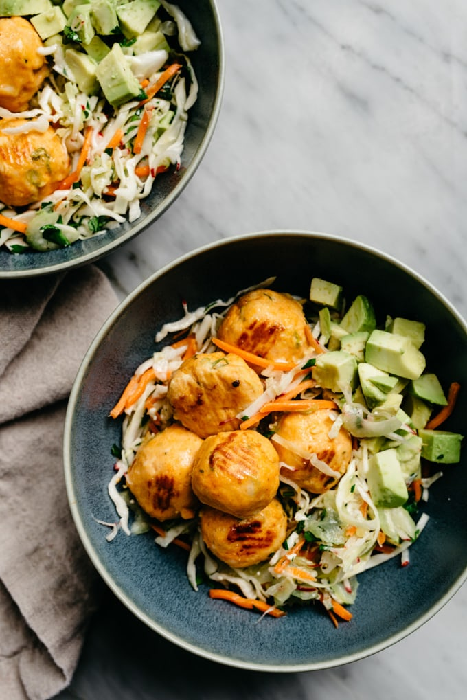 Oven baked buffalo chicken meatballs over coleslaw with avocado in a blue bowl.