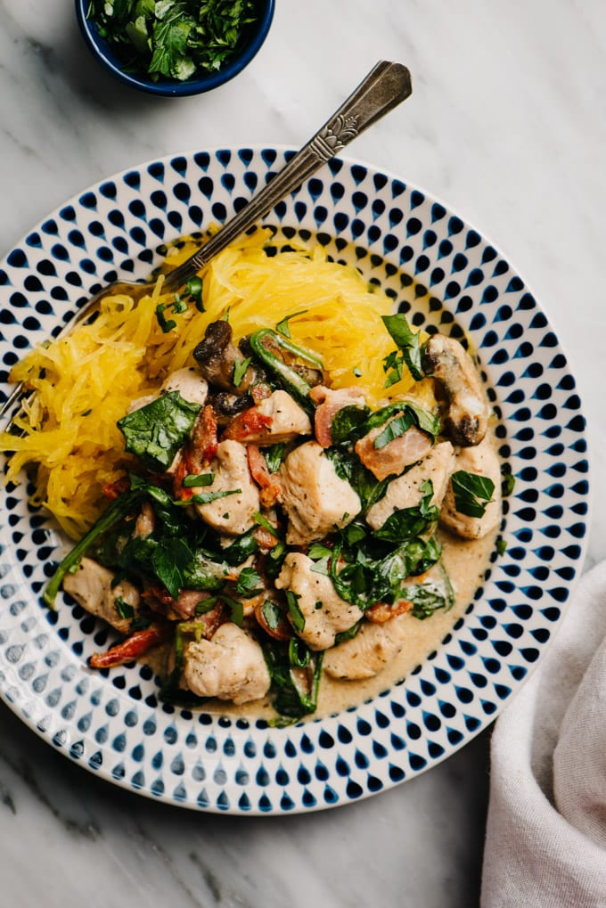 A plate of healthy tuscan chicken with creamy dairy free bacon sauce over spaghetti squash on a marble table with a linen napkin.