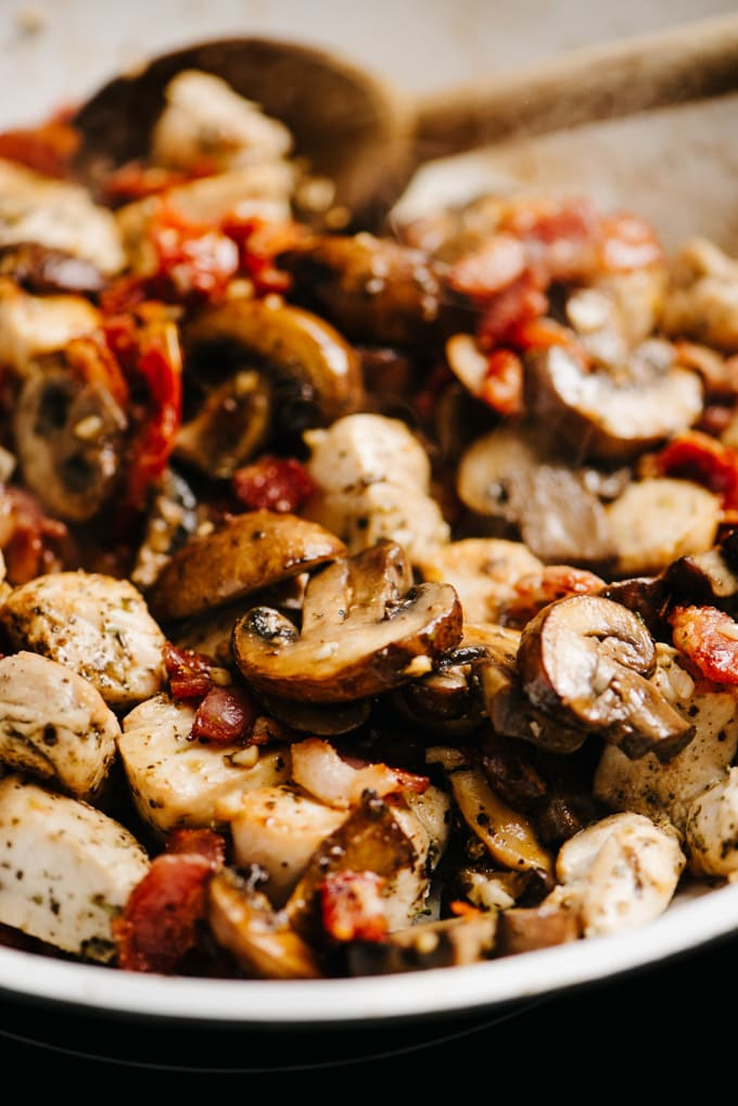 Diced tuscan chicken with sun dried tomatoes, bacon, and mushrooms in a skillet.