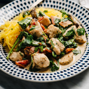 A plate of healthy tuscan chicken with creamy dairy free sauce over spaghetti squash on a marble table with a small dish of fresh parsley on the side.