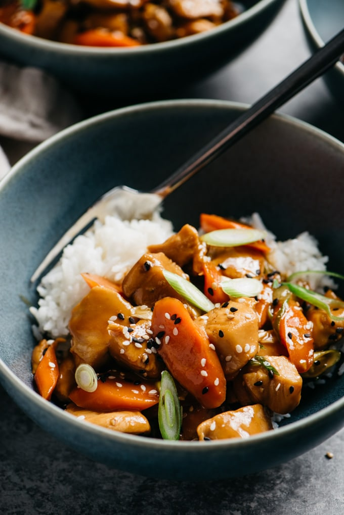 A bowl of honey garlic chicken over white rice with carrots, green onions, and sesame seeds.