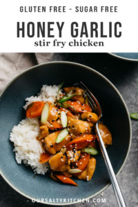 A bowl of healthy honey garlic chicken served over white rice with a fork and a linen napkin.