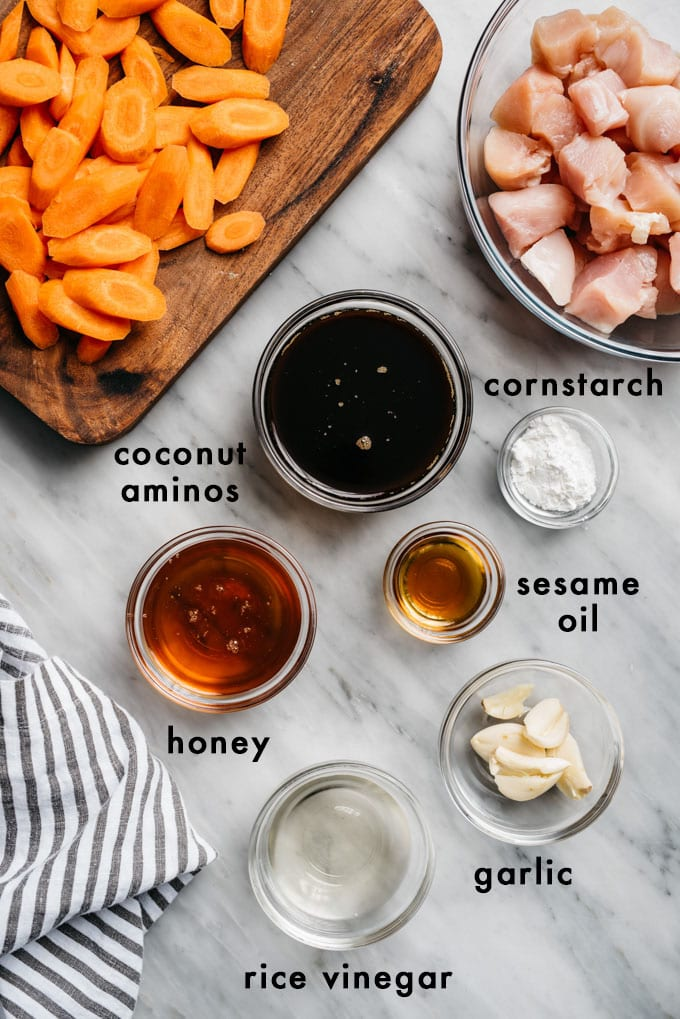 The ingredients for honey garlic chicken stir fry sauce in small bowls on a marble table with cubed raw chicken breasts and sliced raw carrots.