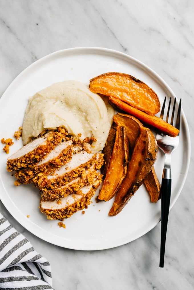 Easy pecan sheet pan chicken dinner on a plate - sliced pecan chicken over cauliflower puree with sweet potato fries.