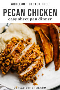 Slices of baked pecan chicken with cauliflower mash and sweet potato wedges on a white plate.