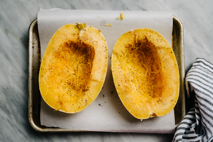 A large spaghetti squash sliced in half, seeds removed, and rubbed with olive oil on a baking sheet.