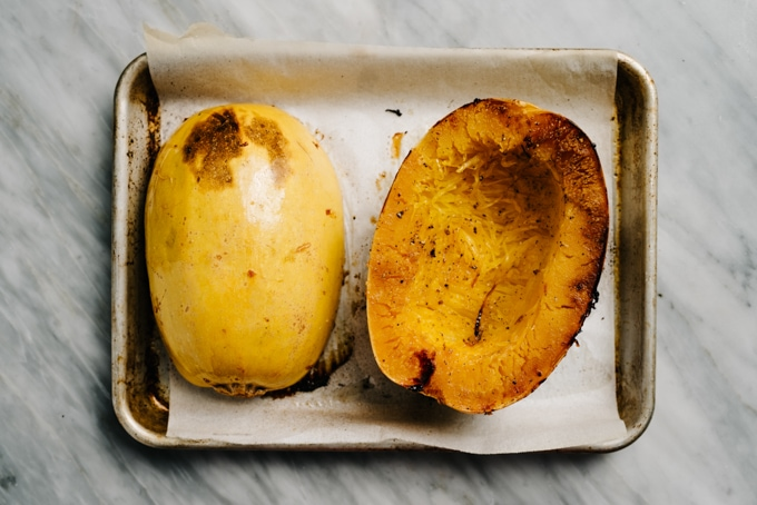 Two roasted spaghetti squash halves on a baking sheet.