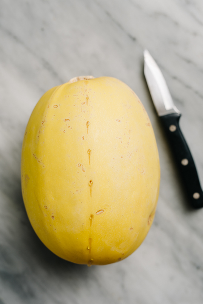A large spaghetti squash scored down the center on a marble table.