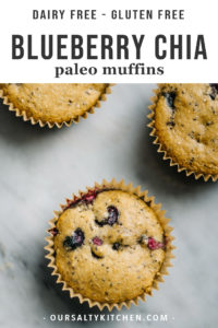 Three paleo blueberry muffins on a marble table.
