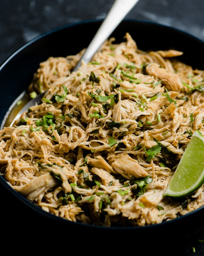 A bowl of slow cooker cilantro lime chicken with a lime wedge and serving spoon.