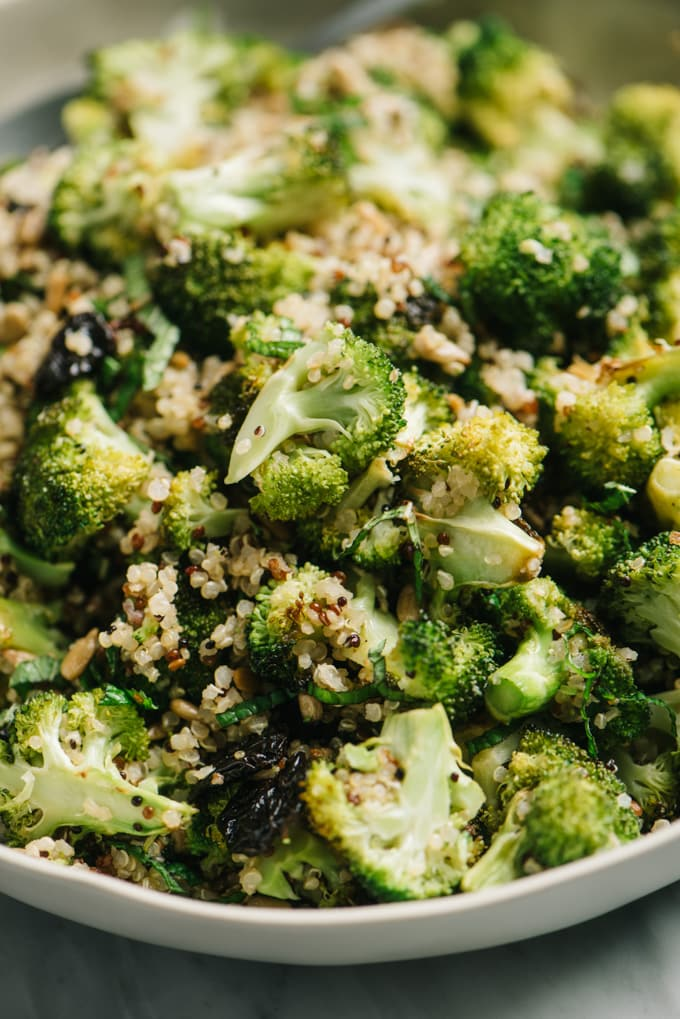 A close-up image of vegan roasted broccoli quinoa salad with sunflower seeds, mint, and dried cherries.
