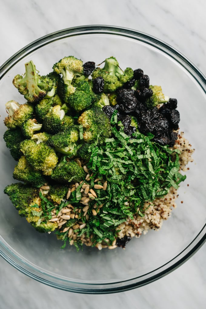 The ingredients for broccoli quinoa salad in a glass mixing bowl.