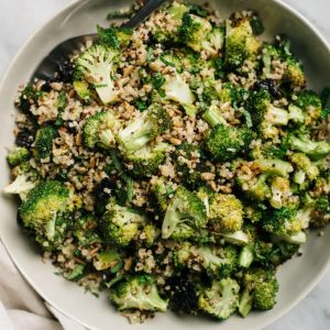 A bowl of vegan roasted broccoli quinoa salad with dried cherries and sunflower seeds.