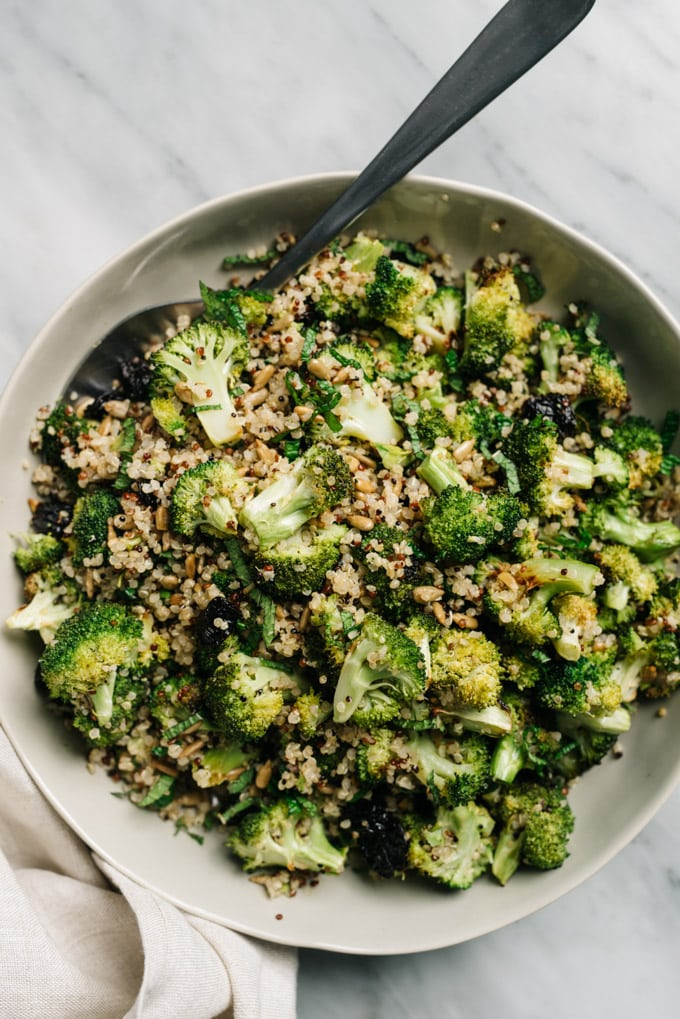 Vegan broccoli quinoa salad with dried cherries and sunflower seeds in a bowl.