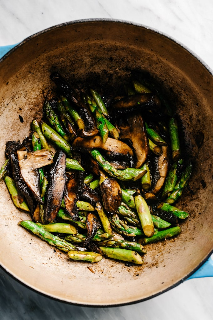 Sautéed mushrooms and asparagus in a dutch oven.
