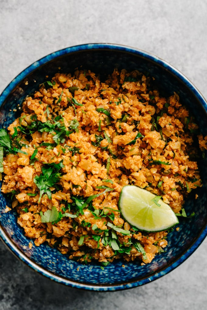 A bowl of vegan mexican cauliflower rice with cilantro and a lime wedge.