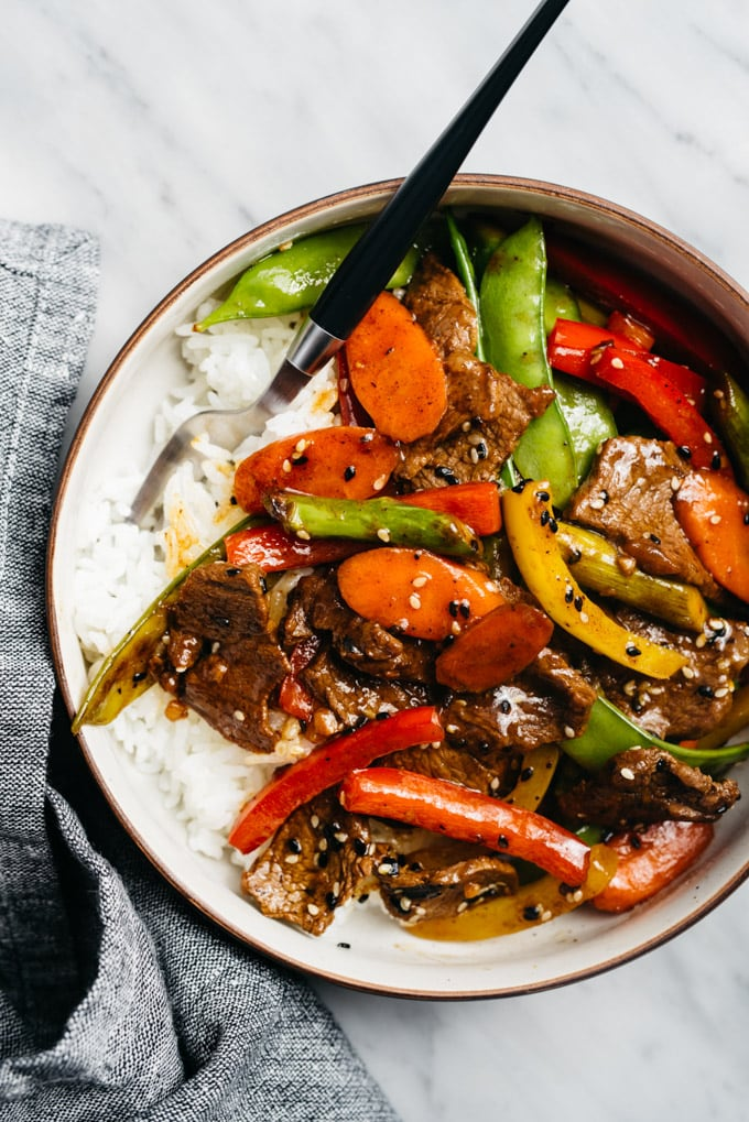 A bowl of gluten free stir fry steak served over rice.