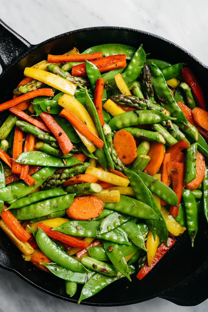 Stir fried carrots, asparagus, bell peppers, and snap peas in a cast iron skillet.