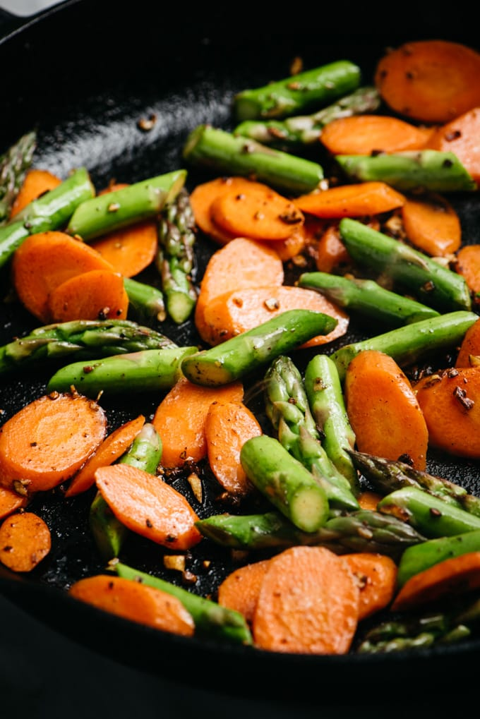 Stir fried carrots and asparagus in a cast iron skillet.