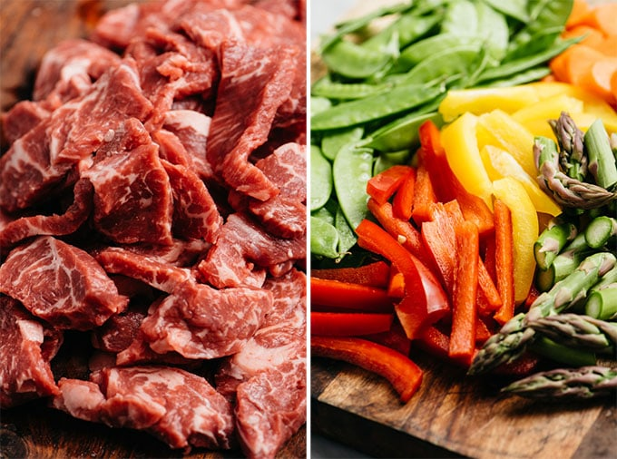 Thinly sliced beef and raw stir fry vegetables on cutting boards.