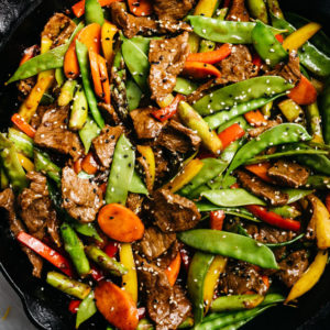 Steak stir fry with vegetables in a cast iron skillet.