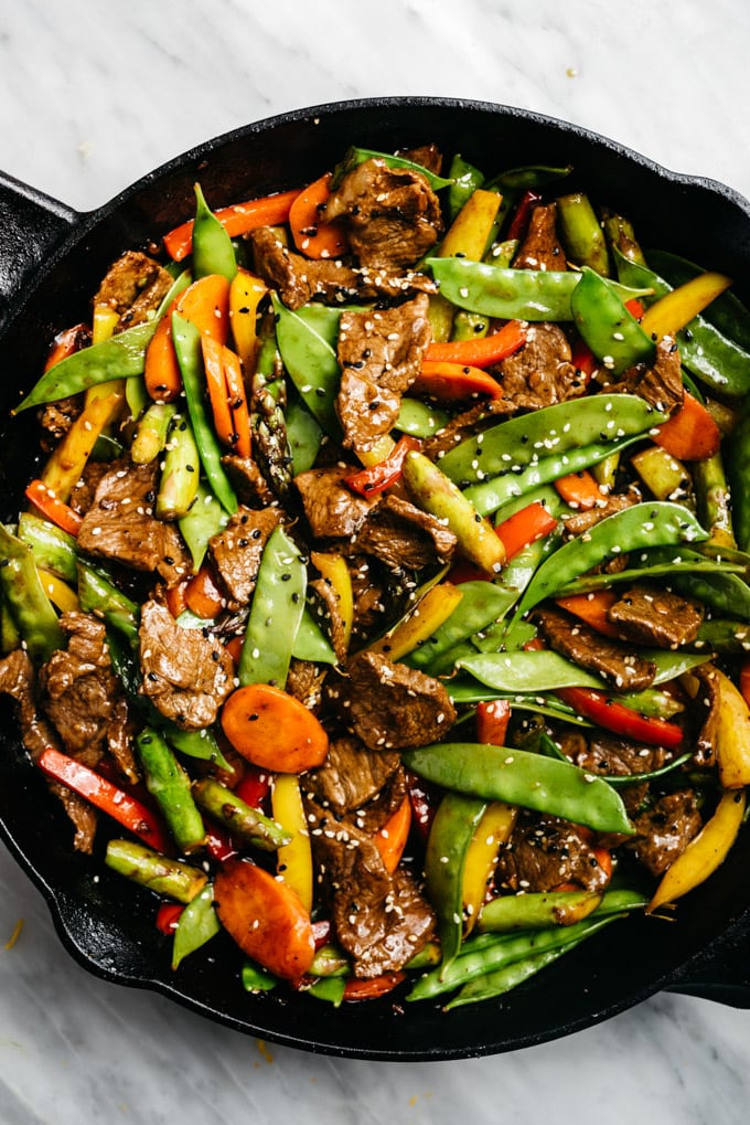 Paleo steak stir fry with vegetables in a cast iron skillet.