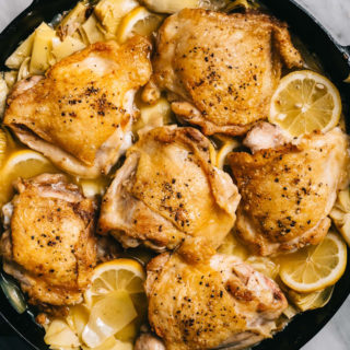 Braised artichoke chicken with lemons, garlic, and tarragon in a skillet on a marble table with a side of roasted potatoes.