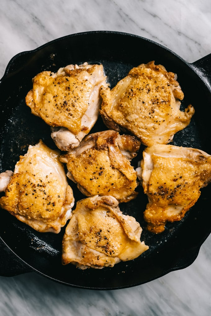 Crispy chicken thighs in a cast iron skillet.