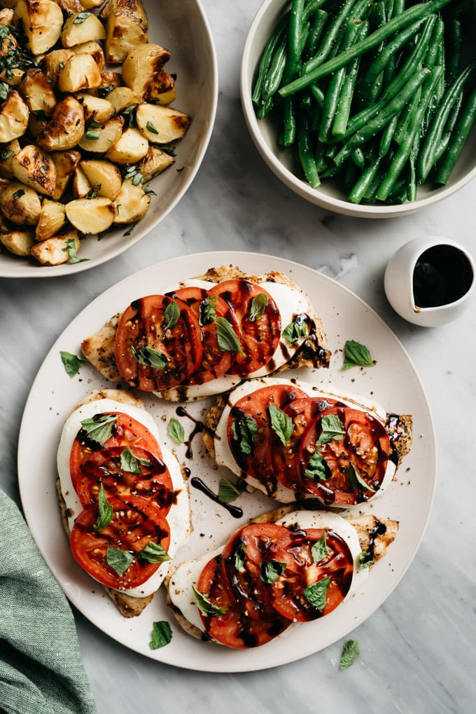 A platter of caprese chicken with tomato, basil, and mozzarella on a marble table with side bowls of roasted potatoes and green beans.