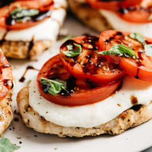 A close-up image of caprese chicken with mozzarella, fresh tomatoes, basil, and balsamic.