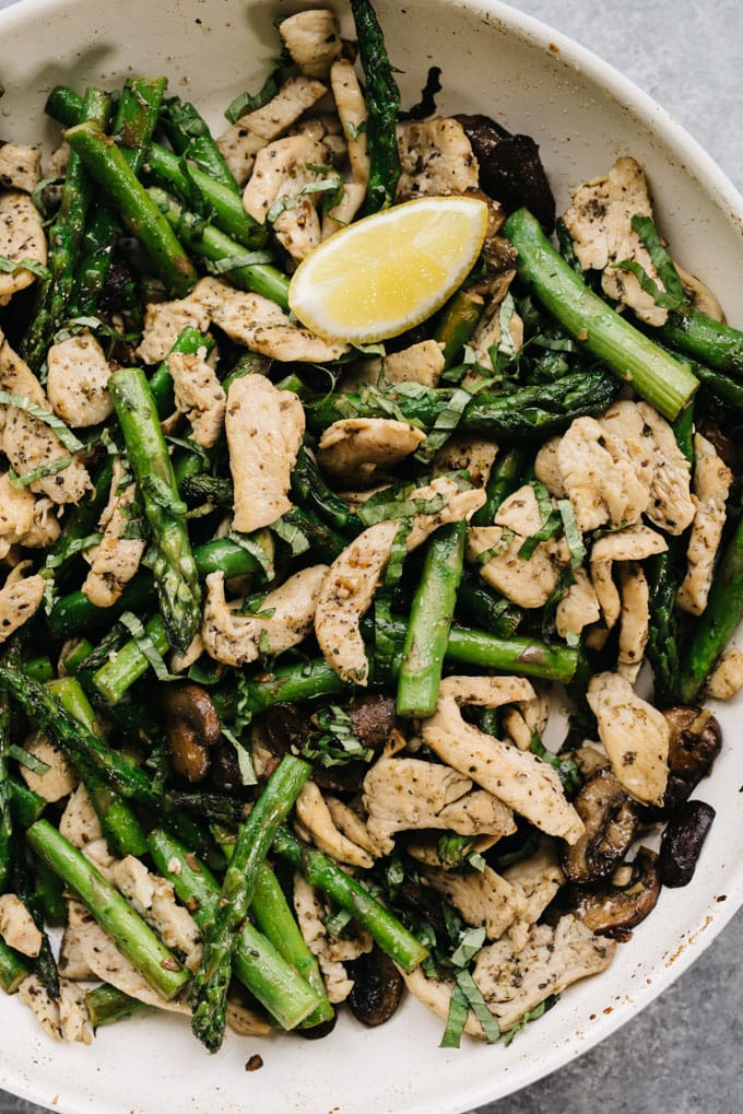 Whole30 and paleo chicken and asparagus recipe in a skillet with mushrooms, lemon and basil.