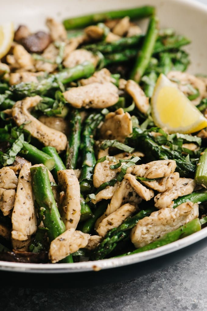 Whole30 chicken and asparagus dinner recipe in a skillet on a cement background.