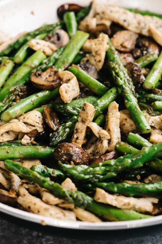 Chicken and asparagus recipe in a skillet with lemon, basil, and mushrooms.
