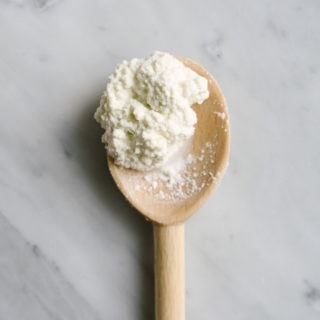 Homemade ricotta cheese on a wooden spoon.