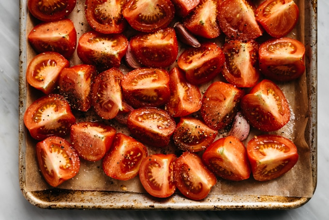 Quartered tomatoes on a baking sheet with whole cloves of garlic.