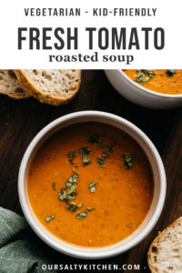 A bowl of roasted tomato soup on a wood table with slices of fresh bread.
