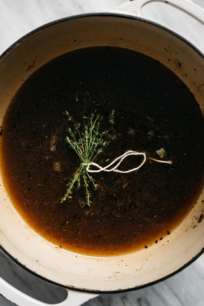 Sautéed onions, balsamic vinegar, broth, and a bundle of fresh thyme in a dutch oven - the base for roasted tomato soup.
