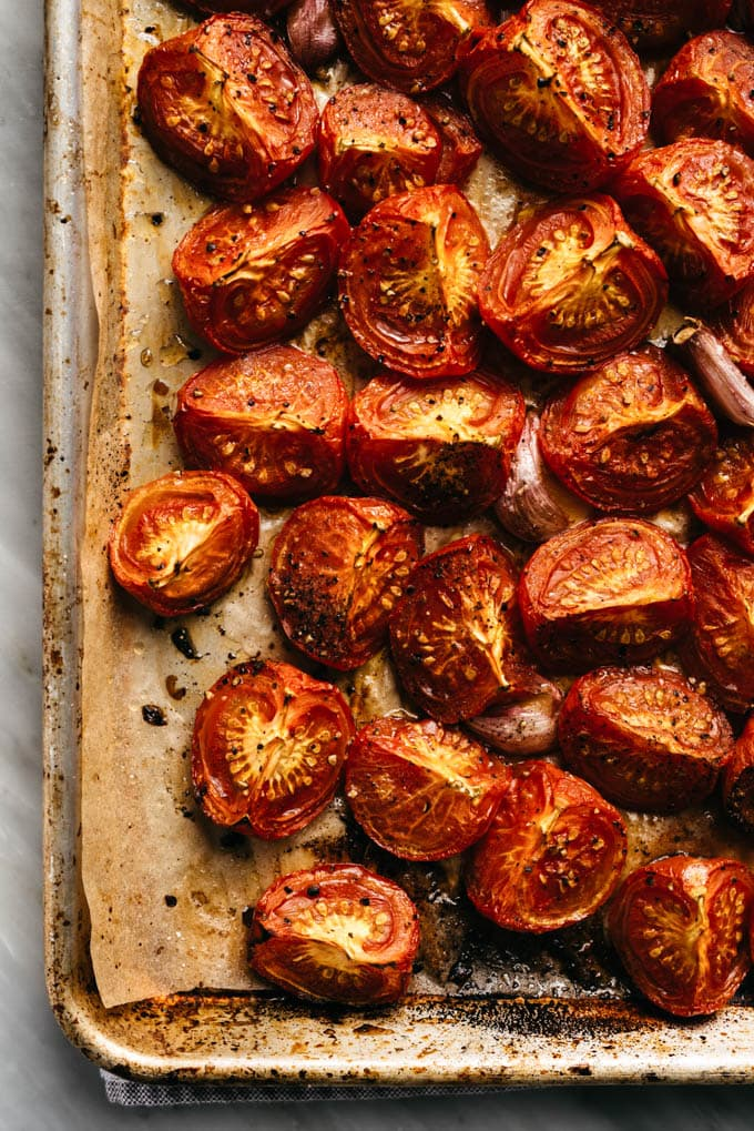 Roasted tomatoes on a baking sheet with cloves of roasted garlic.