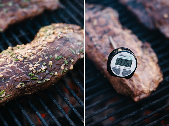 Rosemary marinated flank steak on a grill with an instant read thermometer showing a temperature of 130.