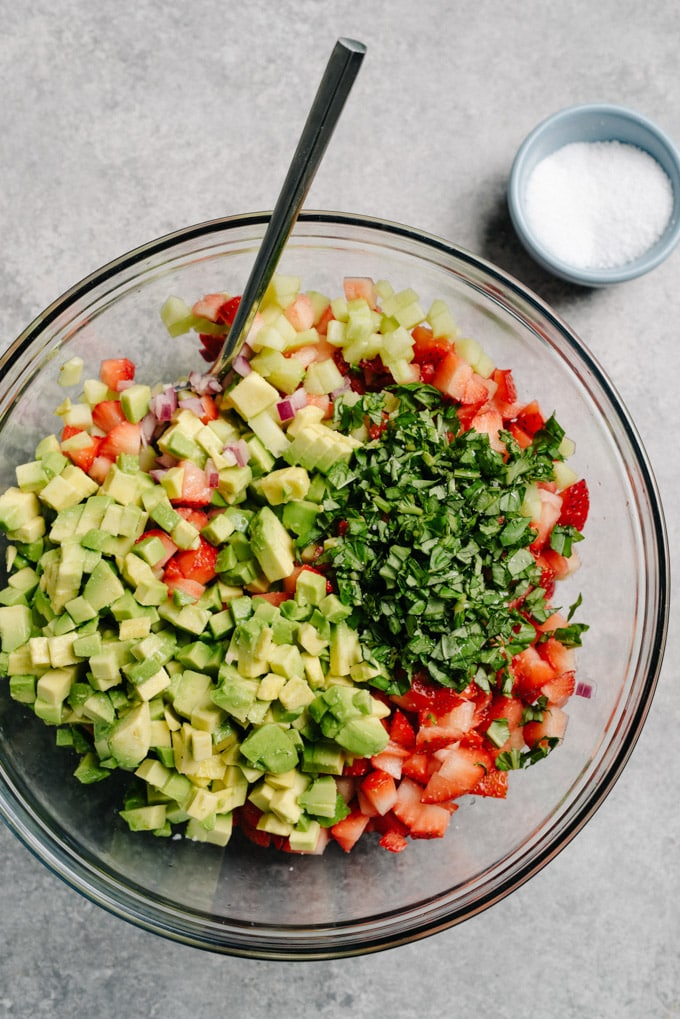 A glass bowl filled with the prepped ingredients for vegan strawberry avocado salsa.