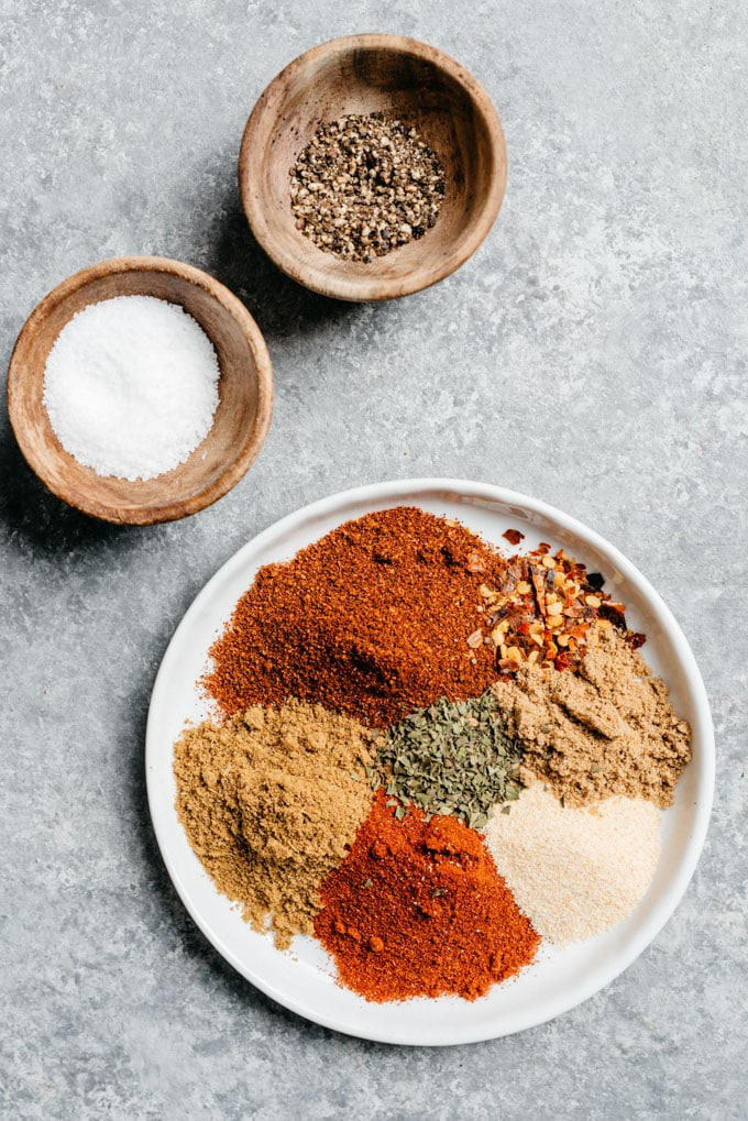The seasonings for homemade beef taco sauce on a small plate with two small bowls of salt and pepper.